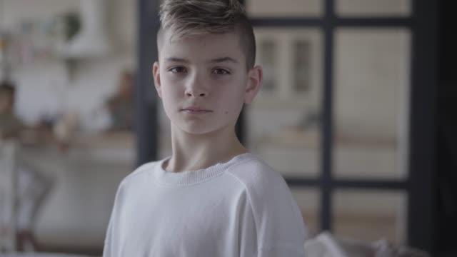 stockvideo's en b-roll-footage met close-up portret van een jonge jongen op zoek in de camera. - wit t shirt