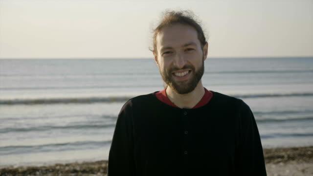 笑顔ビーチで日の出の魅力的な男性の肖像画を間近します。 ビデオ