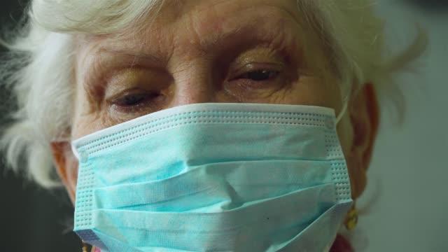 Närbild porträtt av kaukasiska blondin gammal kvinna i skyddande mask på hennes ansikte. Epidemi av influensavirus och coronavirus video