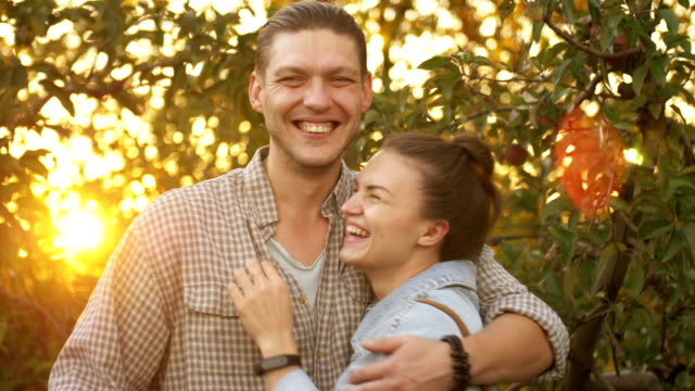 Close up portrait of couple hugging, laughing and smiling outdoors in nature on holiday vacation honeymoon Close up portrait of couple hugging, laughing and smiling outdoors in nature on holiday vacation honeymoon 4K good news stock videos & royalty-free footage