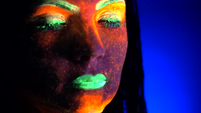 Close up portrait of fashion model woman with braids in neon light. Fluorescent makeup glowing under UV black light. Night club, party, halloween psychedelic concepts
