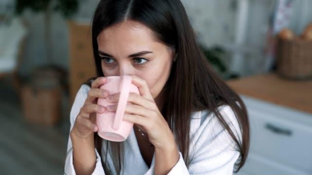 vidéos et rushes de fermez-vous vers le haut de l'verticale de fille boit le thé ou le café et renifle la boisson chaude, le mouvement lent - peignoir