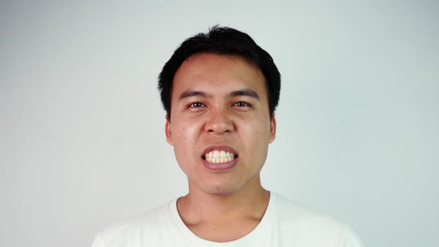 Close up portrait of happy excited Asian man wear white T-shirt expressing gesture of success in a goal at work or victory in a sports game. Emotion and expression concepts.