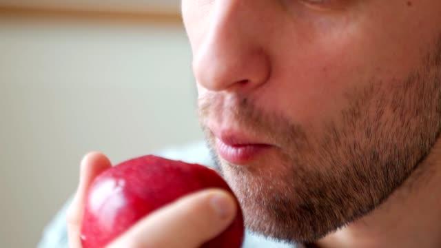 vídeos de stock, filmes e b-roll de feche o retrato da boca masculina comendo maçã vermelha - provando usando a boca