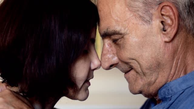 close up portrait of tender reconciliation between an old father and adult daughter - chiedere scusa video stock e b–roll