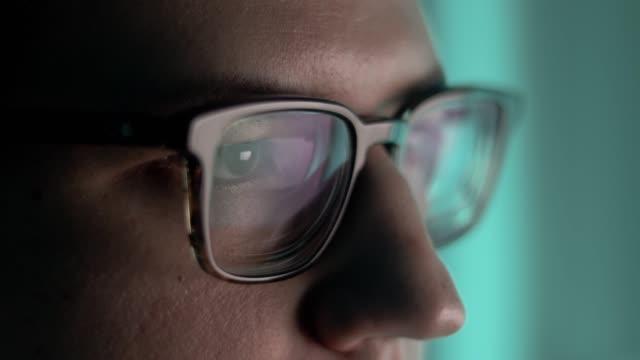stockvideo's en b-roll-footage met sluit omhoog portret van handelaar in glazen met forex grafiekbezinning van beursgrafieken in makelaarglazen. het concept van internationale handel en overwerk in een enorm investeringsfonds. real-time shot - aandelen