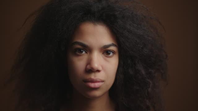 stockvideo's en b-roll-footage met close-up portret van jonge afro-amerikaanse meisje emotioneel op zoek naar camera - curly brown hair
