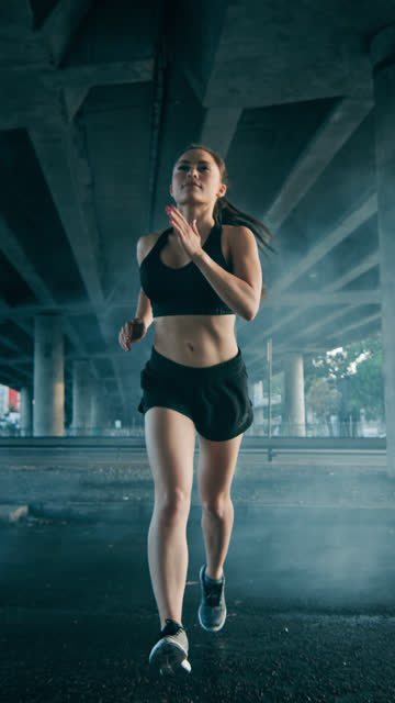 vídeos de stock e filmes b-roll de close up portrait shot of a beautiful confident fitness girl in black athletic top and shorts jogging. she is running in urban environment. video footage with vertical screen orientation - vertical