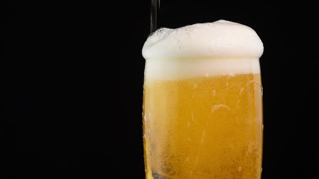 close up pouring lager beer in glass over black - birra video stock e b–roll