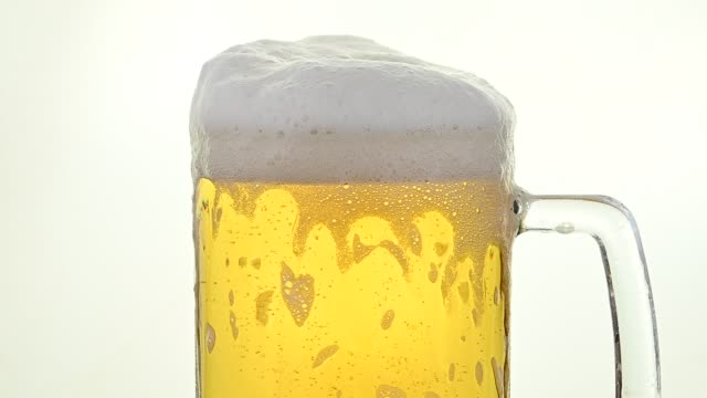 Close up pouring lager beer in glass over white