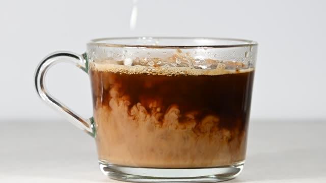 vídeos y material grabado en eventos de stock de cierre vertiendo leche en una taza de vaso de café negro - café negro