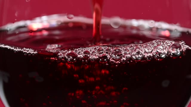 close up pouring red wine in wineglass over red - colore ciliegia video stock e b–roll