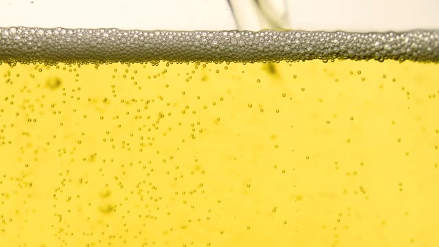 close up pouring soda water with bubbles in glass - gommapiuma video stock e b–roll