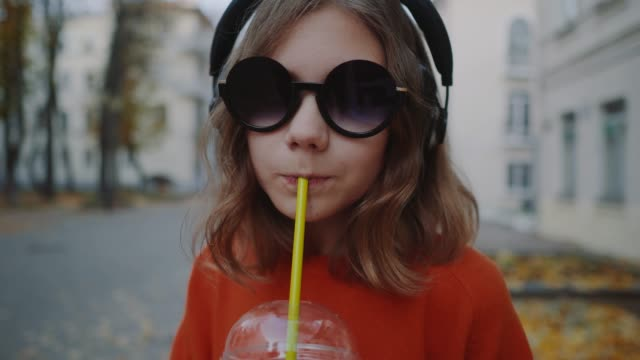 stockvideo's en b-roll-footage met close-up van mooie hipster tiener luister muziek in koptelefoon, drankjes milkshake van een plastic beker, glimlachend en straat wandelen tussen gebouwen. schattig meisje in zonnebril drinkt een drankje met een rietje - milkshake