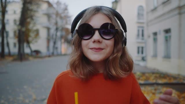 närbild söt hipster tonåring lyssna musik i hörlurar, drycker milkshake från en plastmugg, leende och gågatan mellan byggnader. söt flicka i solglasögon dricker en dryck genom ett sugrör - sugrör bildbanksvideor och videomaterial från bakom kulisserna
