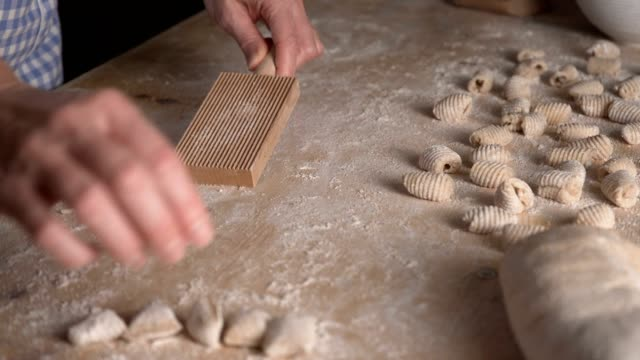 close up process of homemade vegan gnocchi pasta with wholemeal flour making. the home cook rolls the dough on the wooden chopping board , traditional italian pasta, woman cooks food in the kitchen - bio food video stock e b–roll