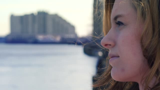 Close up profile of young woman looking from pier video