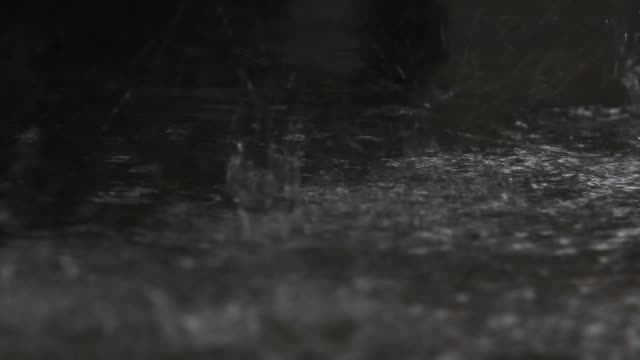 Close up, rain falling and reflection on floor.