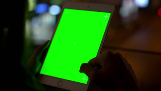 4K Close up rear view of Asian woman's hand holding green screen digital tablet and scratching the touchscreen with blurred city street at night background. City life with technology and social media concept.