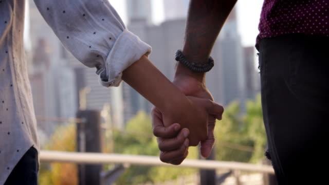 närbild av bakifrån av par hålla händerna samtidigt tittar på manhattan skyline - skjuten i slow motion - hålla handen bildbanksvideor och videomaterial från bakom kulisserna