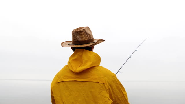 close up rearview of fisherman in yellow raincoat throws fishing tackles with spinning rod in slow motion - wędkarstwo filmów i materiałów b-roll