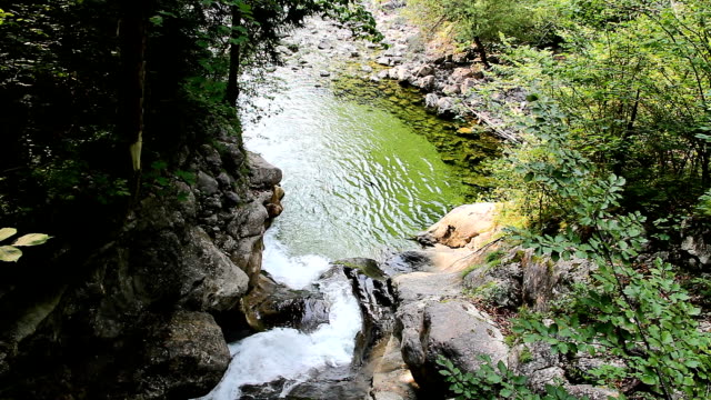 Close up Rindbach waterfall from wooden bridge with forest and small lake. Austria alps mountain