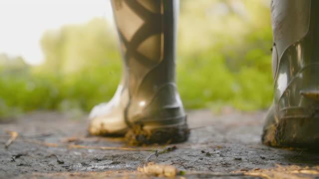 vidéos et rushes de fermez-vous vers le haut de la botte de pluie en caoutchouc avec le travail de boue sur l'endroit sale - bottes