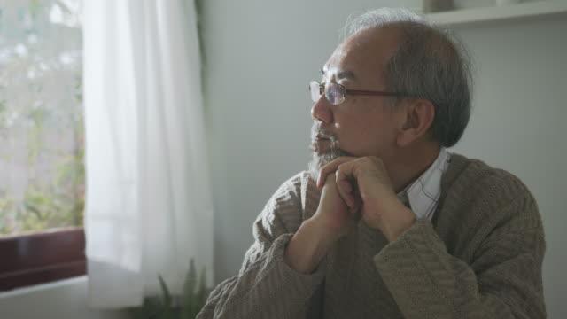 vídeos de stock, filmes e b-roll de close-up : triste velho aposentado de cabelos grisalhos avô asiático sentado sozinho na mesa na janela chato ficar em casa auto-isolamento quarentena sentindo-se depresso em problema de saúde mental. - contemplação
