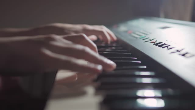 vídeos de stock e filmes b-roll de close up scene side view of student hands playing practicing improvising keyboard at night for a jazz piano online class at night during the pandemic of covid-19 coronavirus, social distancing. - piano