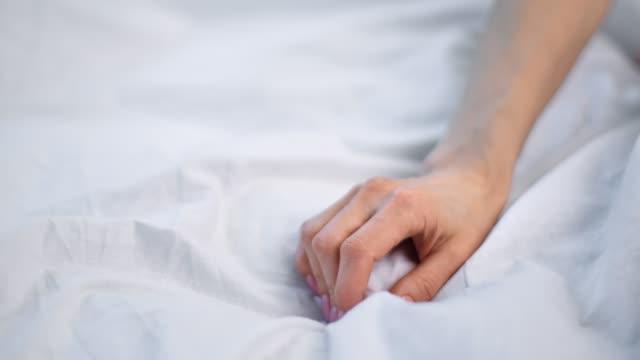 Close up seductive female hand touching soft white sheet. Shot on RED Raven 4k Cinema Camera