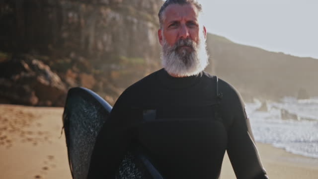 ビーチでサーフボードを運ぶシニアハンサムな男を閉じる - サーフィン点の映像素材/bロール