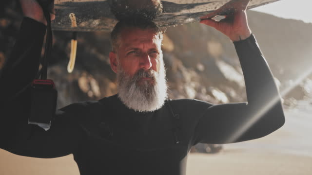 close up senior handsome man carrying surfboard at the beach - przystojny filmów i materiałów b-roll