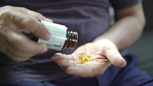 Close up Senior man hands opening bottle of medication and pouring pills into palm of his hand