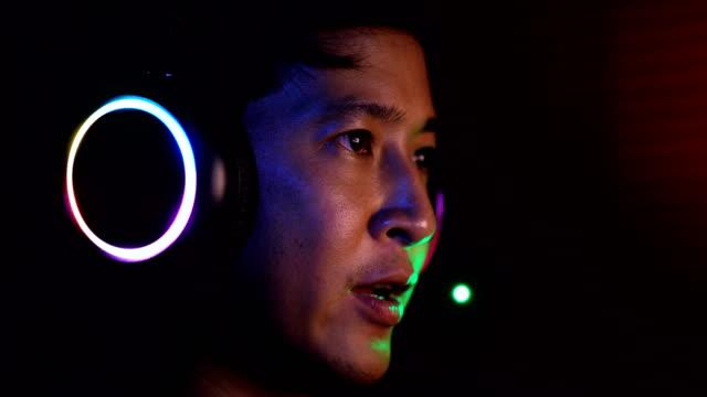 schließen sie serious asian esport player spielen videospiele mit seinem headset. - computerspieler stock-videos und b-roll-filmmaterial