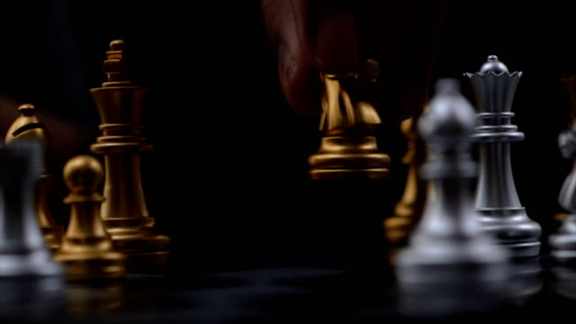 schließen sie die hände des menschen, die goldenes und silbernes schach spielen wählen fokus flache tiefe des feldes - könig schachfigur stock-videos und b-roll-filmmaterial