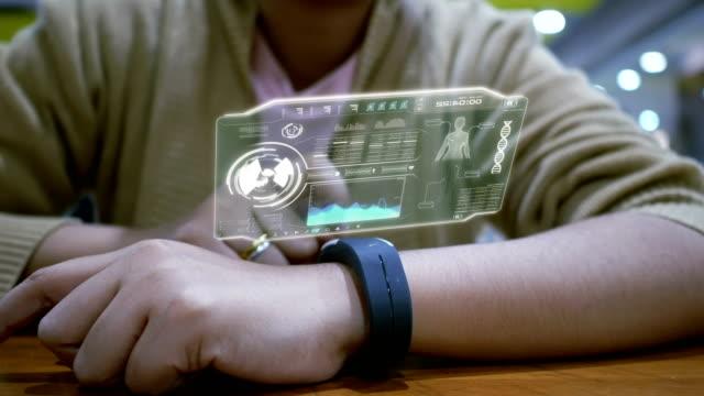 mani ravvicinate di donna che utilizzano l'orologio intelligente con interfaccia utente hud per l'applicazione cyber futuristica e il concetto di tecnologia - computer indossabile video stock e b–roll