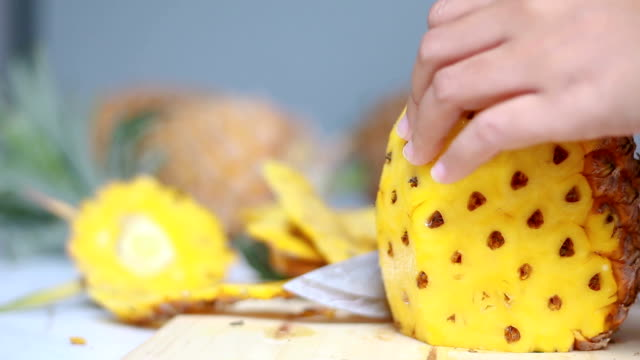 Close up shot hands of women using kitchen knife to cutting and peeling ripe pineapple shallow depth of field with ambient sound Close up shot hands of women using kitchen knife to cutting and peeling ripe pineapple shallow depth of field with ambient sound peeled stock videos & royalty-free footage