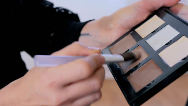 Close up shot. Make-up artist taking corrector from makeup correcting palette video