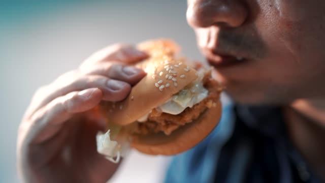 Close up shot men are eating hamburgers. happily