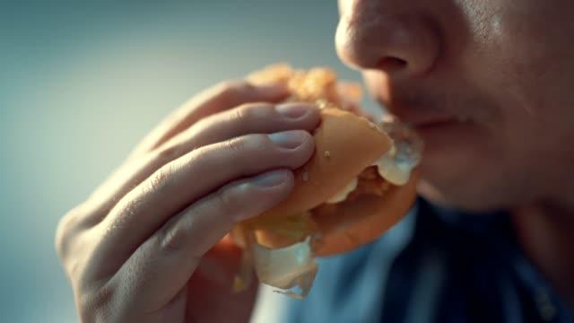 클로즈업 샷 남자는 햄버거를 먹고 있다. 행복 - burger and chicken 스톡 비디오 및 b-롤 화면