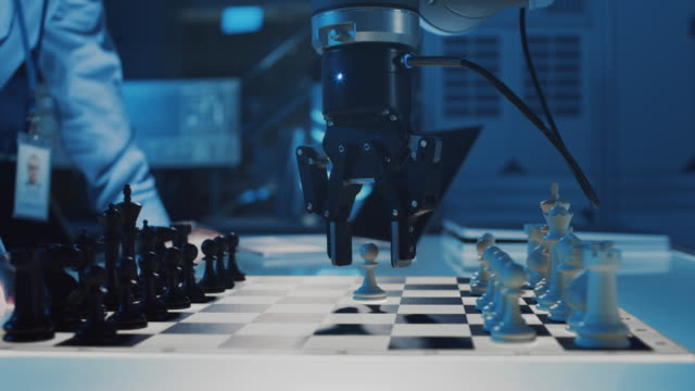 vídeos de stock e filmes b-roll de close up shot of a artificial intelligence operating a futuristic robotic arm in a game of chess against a human. robot moves a pawn. they are in a high tech modern research laboratory. - xadrez