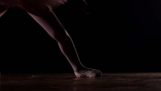 close up shot of a ballet dancers feet as she practices in the dark studio video
