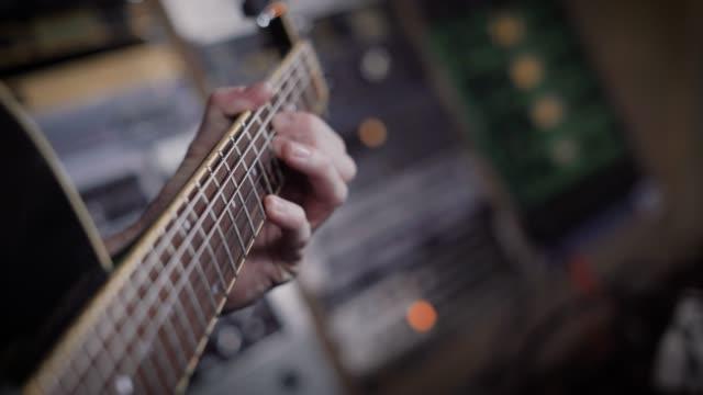 レコーディング スタジオで楽器を演奏、低音のギタリストのショットを閉じる - ミュージシャン点の映像素材/bロール