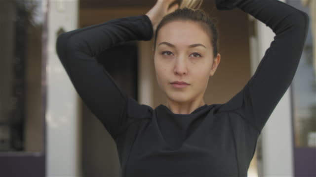 stockvideo's en b-roll-footage met close-up shot van een mooie aziatische vrouw zit op haar veranda, en zetten haar in een paardenstaart - paardenstaart haar naar achteren