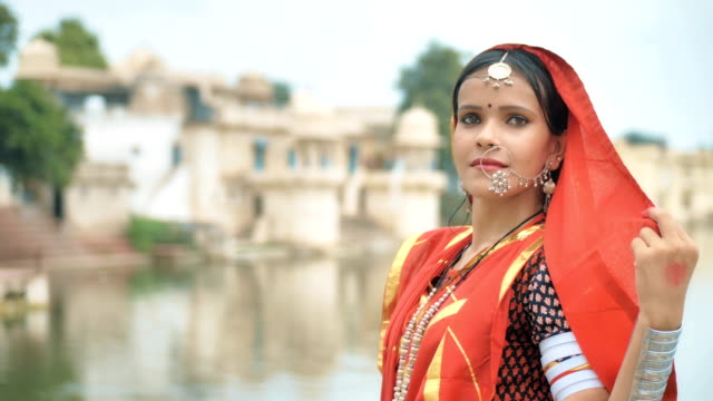 A close up shot of a Beautiful woman looks confidently into a camera beside a lake Indian classical dancer in a traditional cloths looks into a camera with a smile while performing a dance step. A close up shot of a Beautiful woman looks confidently into a camera beside a lake sari stock videos & royalty-free footage