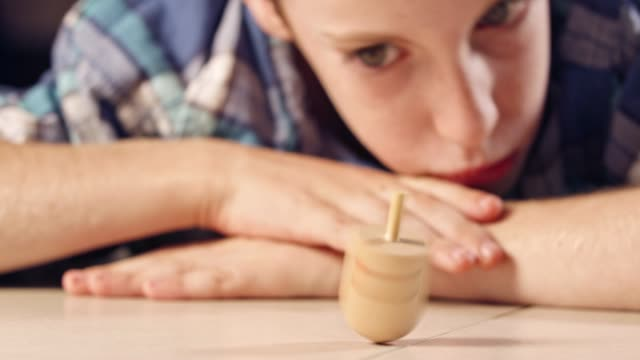 Close up shot of a boy spinning a Hanukka dreidel on the floor Close up shot of a boy spinning a Hanukka dreidel on the floor hanukkah stock videos & royalty-free footage