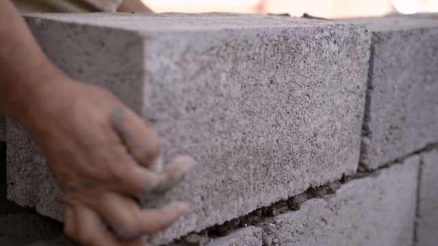 close up shot of a builder working on a site and bulding a wall - concrete architecture stock videos & royalty-free footage