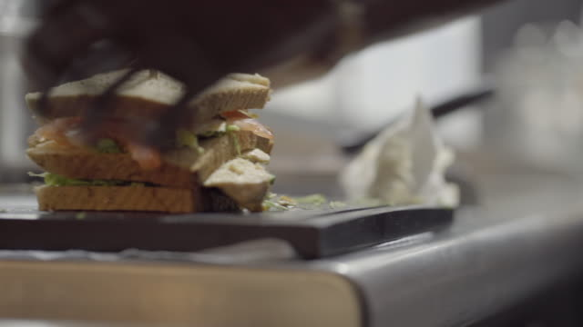 stockvideo's en b-roll-footage met close-up shot van een club sandwich die in helften wordt gesneden - sandwich