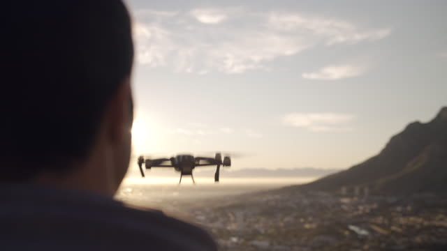 vídeos de stock e filmes b-roll de close up shot of a drone flying over the city and into the sunset - cinematic gimbal shot - man joystick