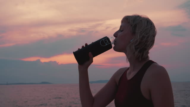 close up shot of a female who finished her run, listening to the music and drinking the water from her reusable glass bottle. - tap water filmów i materiałów b-roll
